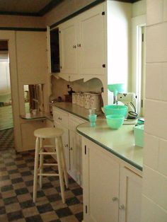 Green and beige vintage kitchen. I love the little pass-through to what must be a butler's pantry!