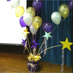 I made this decoration for our award ceremony using school colors.  There were four on the stage and connected by helium filled balloon arches.  Each one contained a latex balloon bouquet with a mylar star balloon to add height (not seen in the photo).  The pots were recycled planters from plants I bought and covered with purple transparent wrapping paper.  The tubes were pex piping (plumbing) which bend and spray painted in gold.