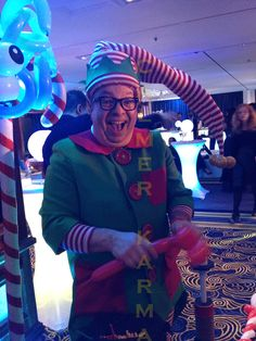 Cheeky Christmas Elf balloon modeller to hire.  This artist is like no other and can build balloon models that will blow your mind with LED included, bells and a whole variety of novelties to make his work stand out and create a luxury felling. Perfect for family friendly events. www.calmerkarma.co.uk Tel:  0203 602 9540
