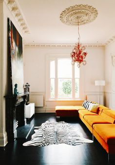 The yellow sofa matched with the animal fur rug, black floor, hanging chandelier gives a very modern vibe I love this room!