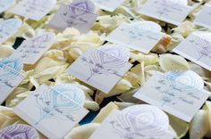 """DIY peacock escort cards.  ordered folded cards. Peacock stamp and ink.  Stamped cards, used razor to cut around so they would """"pop"""" out. Printed names and tables on clear labels    Lacey and Jason   Photos by Realities Photography  http://www.realitiesphotography.com"""