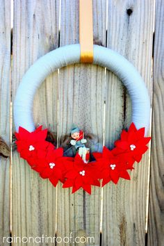 I am dying over how adorable that little elf is! This is such an easy and pretty wreath - very classic! Christmas Wreaths via RainonaTinRoof.com