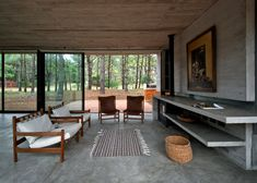 This concrete cabin has textured walls which mimic is wooden surroundings. The central living space is all glass and flanked by concrete boxes. Click through for more images of this Luciano Kruk Arquitectos design.