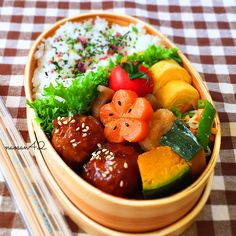 bento lunch inspiration. looks like glazed carrot flower with black sesame seeds, fried japanese pumpkin, tamagoyaki, meatballs with sauce and white sesame seeds. cant figure out the fukirake (sp?) on top of the rice.