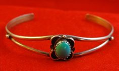 SoVintageous is offering this adorable vintage handmade sterling silver and turquoise Navajo Native American cuff bracelet.  The turquoise cabochon is set in a jagged (tooth-like) bezel in the middle