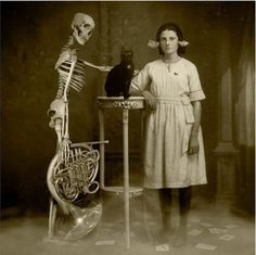 Creepy cat - Vintage photograph of weird woman, black cat and a skeleton holding a tuba.