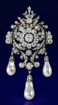 An impressive Victorian natural pearl and diamond brooch. Centring an old cushion-shaped diamond, set within a surround of ten smaller cushion-shaped diamonds and further scroll borders of graduated diamonds, suspending three natural pearl drops. With pendant fitting and detachable brooch fitting.