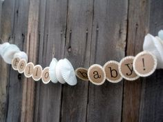 Baby Shower Banner.  Brown kraft paper with white cupcake liners!  So cute.