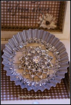 Vintage Ornament Idea - a tart tin, old paper, a piece of tinsel garland and a vintage brooch.