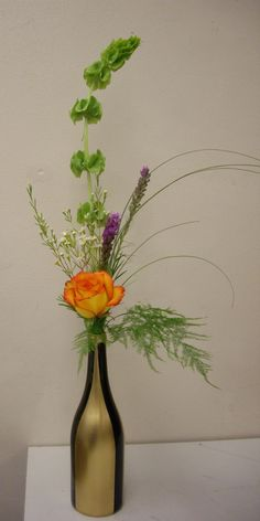 Bud Vase Arrangement that was created as an example for my Advanced Floriculture students to follow.  I also painted the bottle!  I used Bells of Ireland, Liatris, a Rose, Wax Flower, Plumosa Fern & Bear Grass.