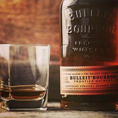 A bottle of Bulleit Bourbon and a glass with a shot of bourbon
