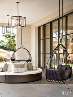 decoracion jardin, terraza con sillones colgantes y sofá redondo, suelo de baldosas, lámparas colgantes y ventanal