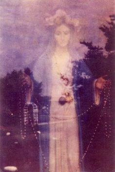 NUESTRA SEÑORA DE GARABANDAL, fotografía tomada a la Virgen durante una aparición (España), y pueden verse a través de su figura -coronada de rosas- la plaza, los árboles, etc.