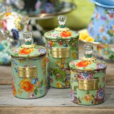 Flower Market Canisters - Green: Flour, sugar, and coffee might seem the most obvious of contents with which to fill a set of three Flower Market Canisters, but the possibilities are endless! Keep them in the kitchen with coffee beans and tea bags, cookies and candies, or dog biscuits and birdseed-or invent new uses around the house. Color glazed in green, each Canister is decorated with hand-applied fanciful botanical transfers that recall a lush English garden in the peak of summer.