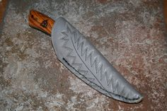Damascus steel blade with a Cocobola handle. A small trinity pyrograph in the handle and a cowboy boot sheath.