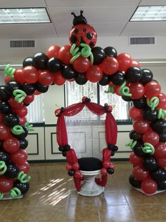 Ladybug theme baby shower party. Mother wicker chair with balloon arch.