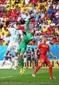 Thibaut Courtois of Belgium makes a save against Martin Demichelis of Argentina