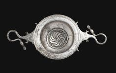 Greek silver strainer, 350-300 B.C.  The hemispherical bowl with lathe-turned rings on the broad flat rim, the center with perforations arranged in a whorl, surrounded by two perforated bands, the two flat handles narrowing to duck-head finials, forming a hook with its rounded elongated neck, one facing left, one facing right, with four small volutes emerging from the base of each handle, 22.2 cm long. Private collection