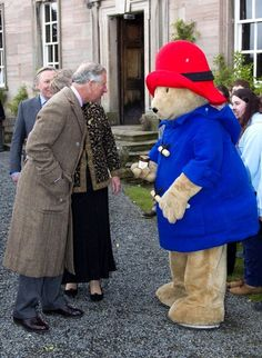 Prince Charles chats with Paddington Bear.  Probably about very important things, like marmalade. :)