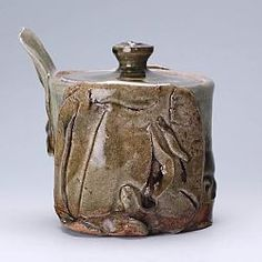 This is a thrown lidded stoneware jar by Terry Bell Hughes decorated with an elephant motif on both sides.