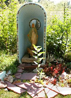Marian shrine created with painted bathtub and a small round mirror attached behind to create a halo.
