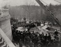 People gathered around crate containing the coffin of President Abraham Lincoln on September 26, 1901. After attempts were made to steal Lincoln's corpse, Robert Todd Lincoln decided that it was necessary to build a permanent crypt for his father. Lincoln's coffin would be encased in concrete several feet thick, surrounded by a cage, and buried beneath a rock slab.