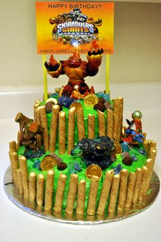 Skylanders cake! Loved how it turned out! I used rock candy as the prisms, choc. candy coins, choc. almonds (found at sprouts) for rocks, Pirouette cookies for the wood around the whole thing, and then added real skylanders(I covered the bottoms in tape for protection and easy clean up). For the sign I found a basic picture online, then added my boys names and attached it to straws and stuck them in the cake. It was a huge hit at our birthday!