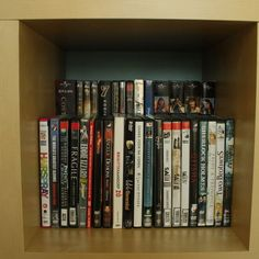 Double DVD storage space by placing a raised shelf in the back of a bookcase. http://hative.com/creative-diy-cd-and-dvd-storage-ideas-or-solutions/