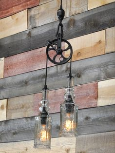 """Whisky Industry: A mixture of steampunk and industrial design, this pendant lamp (""""The Warehouser"""") is fashioned out of two recycled whiskey bottles, a decorative pulley and vintage-style braided cloth wire. Choose from four finishes: black, copper, oil-rubbed bronze or antique brass."""