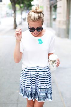 Plain tee tucked into a striped skirt and a top knot