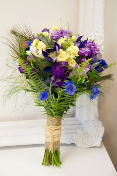 Blue, purple, cream and soft yellow wedding flowers with peacock feathers by Living Fresh Flower Studio and School