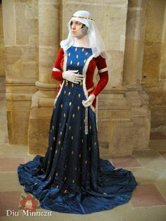 Surcoat and kirtle with wimple and kerchief. 14th century. Note the metal dress ornaments on the surcoat.