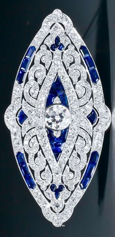 An Art Deco sapphire and diamond brooch, by Mauboussin Paris, circa 1924. Set throughout with old European- and single-cut diamonds, and calibré-cut sapphires. The openwork platinum mount shows the typical 'millegrains' finish. Unsigned. Accompanied by the Mauboussin certificate of authenticity. Numbered, French maker's mark and French assay marks for platinum and 18 karat gold. #Mauboussin #ArtDeco #brooch