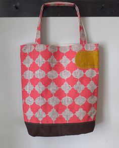 """Made of a luxurious hand printed linen and lined with an organic cotton  interior. Each bag has one interior pocket of contrasting pattern  measuring 9x12"""".  This is the perfect everyday tote. It's great around town whether you pack  up your laptop in it, take it to the library, or use it at the grocery  store. It's just the right size to fit a number of things without having  them get lost in the abyss of a larger bag. These bags also make the  perfect travel companion. Rolls up…"""