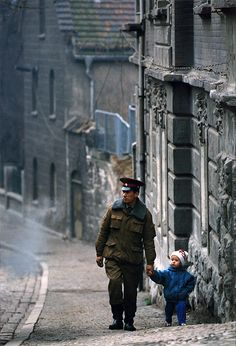 An Ossi soldier looking toward the Wessis walks a young girl down a street just after the fall of the Berlin Wall, East Germany, 1990, photograph by Bob Leverone.