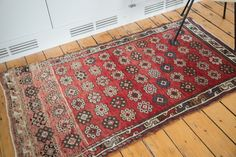 Stunning cherry red rug with stylized pattern of allover flowers in shades of ivory, grey and earth tones.
