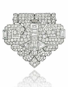 AN ART DECO DIAMOND CLIP BROOCH, BY CARTIER  The geometric stylised arrow head, pavé-set with circular-cut diamonds to a central triangular and baguette-cut diamond highlight, 1934, French marks for platinum, 4.2cm long Signed Cartier, Paris