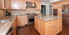 Under cabinet range hood, natural maple Shaker style cabinets with quartz countertop and cork flooring.
