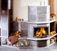 """Fireplace with heated bench, extended mantle, and soapstone chimney.""   www.mainemasonrystove.com"