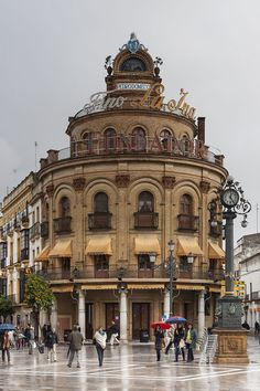 El Gallo Azul . Con motivo de la Exposición Iberoamericana de 1929, la familia Domecq le encarga al arquitecto sevillano que crease un edificio que serviría para embellecer el cruce entre la calle Larga y la calle Santa María, en la plaza homónima al edificio, como regalo a la ciudad. El Gallo Azul es un paso obligado en el centro histórico y comercial de Jerez y quizás por ello, es uno de los lugares más fotografiados. Photo by CEphoto, Uwe Aranas / CC-BY-SA-3.0