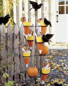 Candy Cone Decorations:  Halloween entertaining is all about scaring up creative ways to celebrate the holiday. Neither children nor grown-ups want to miss out on trick-or-treating. Treat every guest to a surprise right at the door, perhaps with candy-filled cones nestled in a vintage plant stand aflutter with feathered crows.