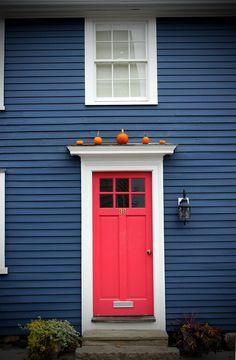 Red Door | Little orange pumpkins above the red door on blue house