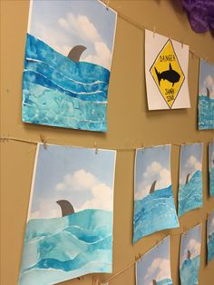 Ripped water color paper to create ocean on sky paper with shark fin art project for kids