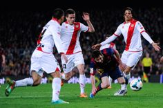 Lionel Messi of FC Barcelona duels for the ball among Rayo Vallecano de Madrid players during the La Liga match between FC Barcelona and Rayo Vallecano de Madrid at Camp Nou on February 15, 2014 in Barcelona, Catalonia.