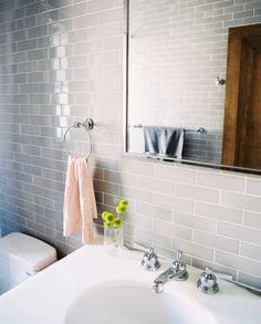 Minimalist Modern Bathroom: Gray subway tile and a striped hand towel in a bathroom .