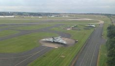 Aerial view of RAF Waddington, taken by Phil Davies from the rear-cabin portal window, this is his view down on the airfield as the aircraft reaches the full wing-over on climb-out. R – Courtesy of Neil Clarke, Lincs and Notts Air Ambulance, we have this image of two famous sisters together – last flying Avro Vulcan XH558 parked near camera with preserved Vulcan XM607 in the distance.