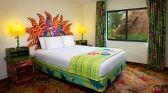 A queen bed with a Zazu headboard flanked by end tables next to a window