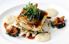 Pan-fried sea bass sits beautifully atop a mound of creamy beans in Mark Dodson's indulgent recipe. A rich Jerusalem artichoke purée and robust red wine jus are perfect accompaniments, while the suggested plating with deep-fried rocket and sun-dried tomat Fish Recipes, Seafood Recipes, Cooking Recipes, Jerusalem Artichoke Recipe, Fish Supper, Artichoke Recipes, Great British Chefs, Sea Bass, Gastronomia