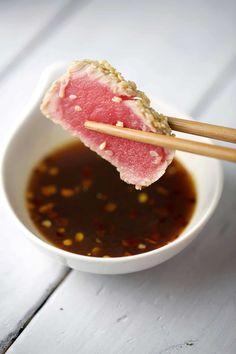 Chopsticks holding seared sesame crusted ahi tuna