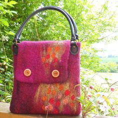 This sweet little hand bag is seamlessly felted (made it all in one piece, no sewing or knitting involved) from merino wool fibre in raspberry,